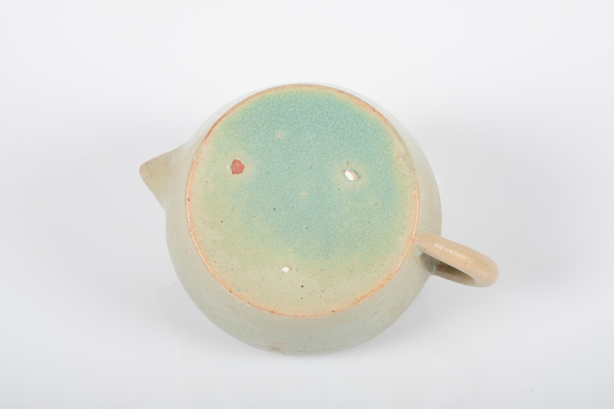 Fløtemugge i keramikk med grønn lasur. Blanke overflater. Buet hank. 2 (har vært 3) små knotter på bunnen, usikker funksjon.