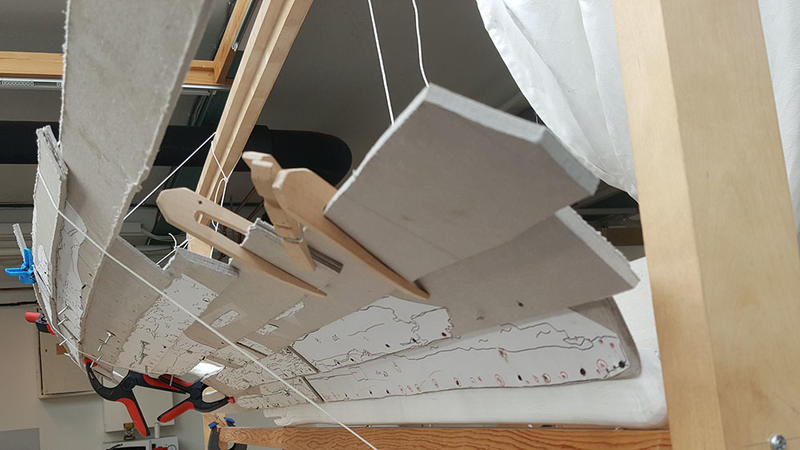 Modellen av Lovundbåten sett akter- og nedenfra. Bord i papp holdes på plass av klyper i tre og snører hengt opp i treramme. (Foto/Photo)