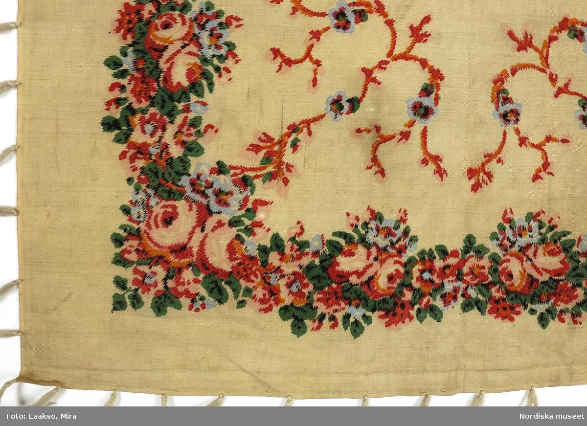 Kvadratiskt halskläde av kyprad yllemuslin, gråvit med tryckt mönster i rosa, rött, grönt, gult  och ljusblått, i mittspegeln  blommslingor i rött/gult med ljusblå blommor och i kanten  en tät bård med bulliga rosor. 2 tråcklade fållar och 2 stadkanter, iknuten mycket gles frans av gråvitt ullgarn. 2 svarta runda stämplar i ena hörnet, den ena  Stockholms (?) hallstämpel, den andra tillverkarstämpel: Magnusson & ... samt i mitten skönjbart Arons Davi... Mönstret imiterar, i förenklad form,  vävda s.k. äkta schalar som var mycket eftertraktade. De finaste vävdes i Norwich, England, eller Paisley och Edinburgh i Skottland i början av 1800-talet. Imitationer i tryck på ylle eller bomull blev moderna bland allmogen kring mitten av 1800-talet och bars ofta som brudschal. Anm. Något solkig, en del fransar saknas.  Har sannolikt inte burits tillsammans med den stickade tröjan litt b. Stämplarna är något svårtolkade eftersom de är delvis otydliga och motsägs av forskning. Det fanns enligt uppgift på katalogkortet en tryckare Magnusson & Reis i Göteborg 1816-1828 och  en J.Magnusson som hade kattuntryckeri I Stockholm endast åren 1820-21. Enligt Henschen var det dock J.J.Amelung som började trycka på ylle, först  1834,  vilket krävde en annan färgkemi, som ingen tidigare kunde.  Amelung tryckte bl.a borddukar som var imitationer av kashmirschalar. Detta halskläde bör alltså vara från tiden efter 1834 vilket också mönsterbilden talar för som liknar 1830-talets schalmönster. Om det som förmodat är Stockholms hallstämpel användes denna  åren 1835-1850 medan Göteborgs hallstämpel ser något annorlunda ut i mitten, se  stämpel på 176.946 /Berit Eldvik 2012-01-03
