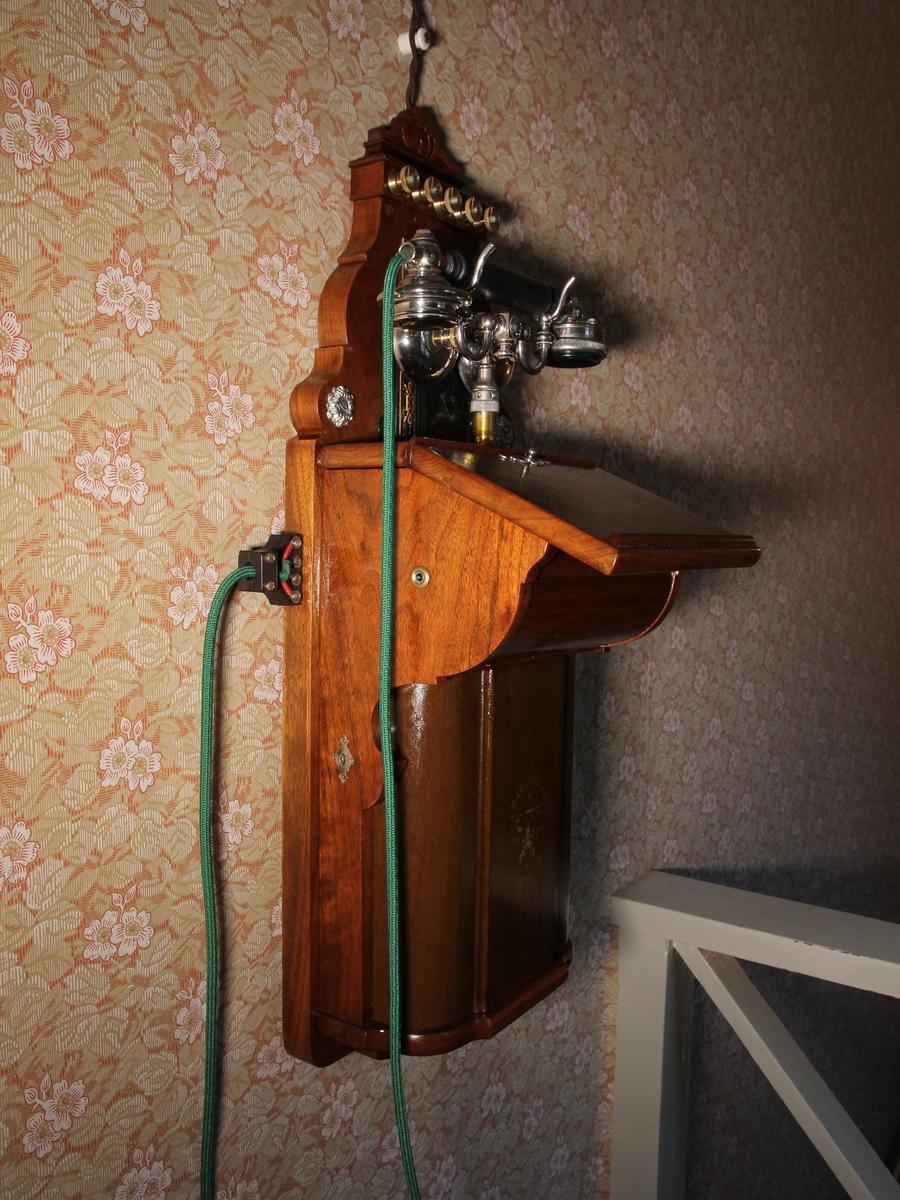 Telefon, väggapparat. Stående rektangulär med snedställd skrivplatta av brunbetsat trä. Klyka av vitmetall, lur och grönt telefonsnöre, Till höger vev. Kompletterad.