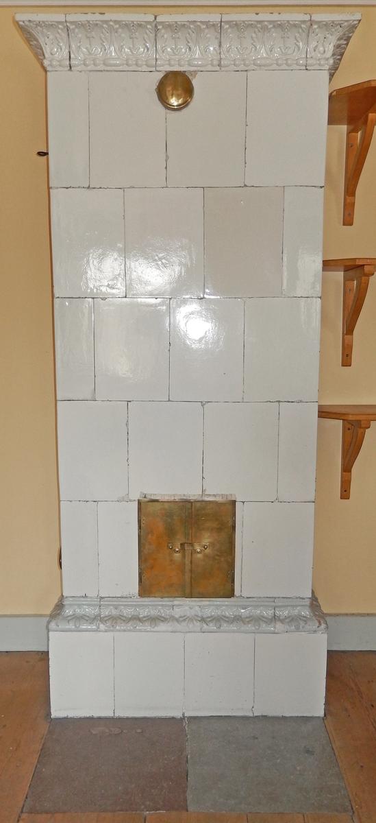 Kakelugn, flat, vitglaserad, kakelugnslucka. Krönlist och fotsims med reliefdekor.