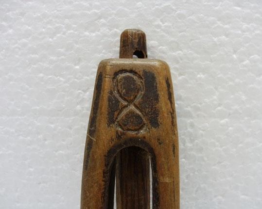 """Anmärkningar: """"Rullsticka"""" av trä, björk, 1787. Två stycken. Den ena avbruten, den andra: Höjd 310 mm Består av en spolformig genombruten kropp, som kan svänga runt en axel, vilken nedtill först bildar den skål, som spolen vilar på, och sedan utdrages i ett långt ovalt skaft. Upptill kvarhålles spolen genom en i ett hål på axeln inslagen plugg. Redskapet är ornerat med inskurna triangulära figurer: (teckning som ej har tolkats). Upptill årtalet 1787 och nedtill bokstäverna K/. . . /D.  Dylika linfästen höllos i äldre tid under armen eller fästet innanför gördeln på vänstra sidan"""