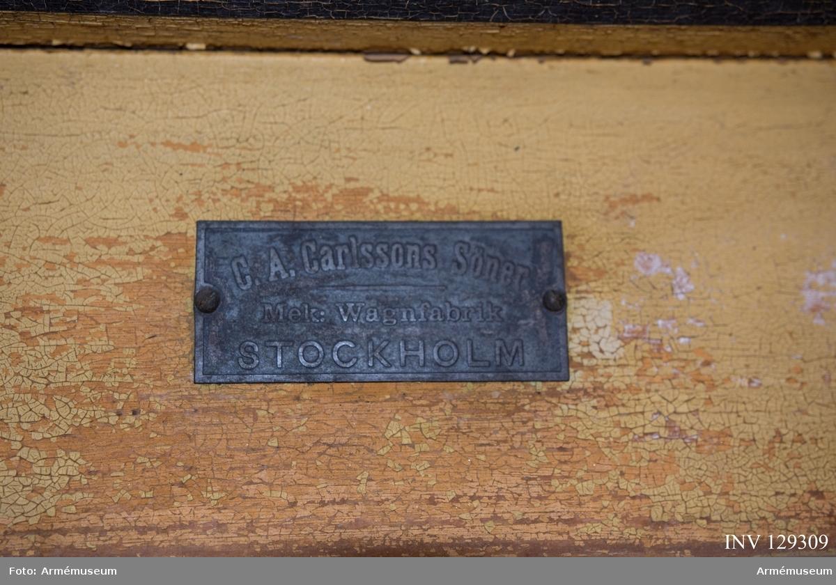"""Gulmålad Tillverkad av C.A. Carlsson och söner. Emblem på sidan: """"DSF"""" - Drottning Sofias Förening till understödjande för härens sjukvård. Föreningen fanns mellan 1900-1913, då den slogs ihop med Röda Korset."""