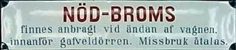 """Långsmal rektangulär skylt av emaljerad plåt med röd och ljusblå text på vit botten. Svart ram. Text: """"NÖD-BROMS finnes anbragt vid ändan af vagnen, innanför gafveldörren. Missbruk åtalas."""""""