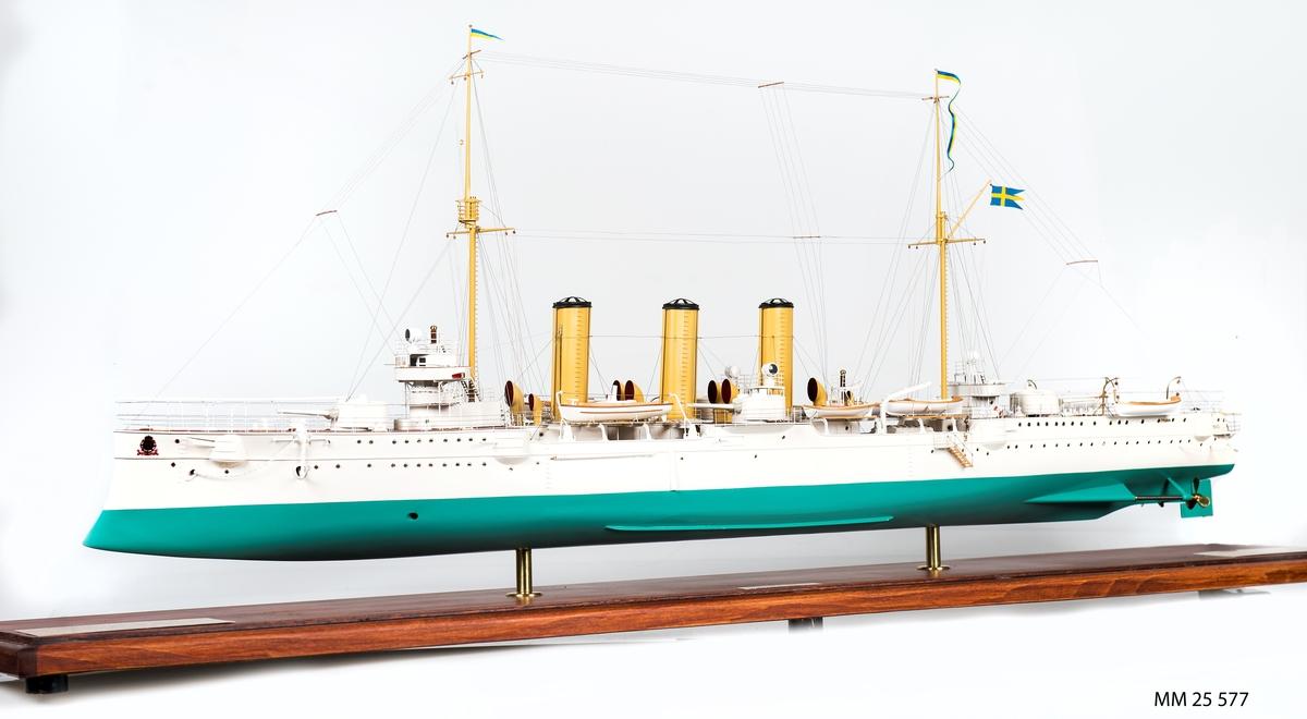 """Fartygsmodell av pansarkryssaren Fylgia i skala 1:100. Detaljerad modell av Fylgia i originalutförandet. Vitt skrov, grön botten, tegelrött däck. Tre skorstenar samt master i gult. Tio skeppsbåtar, tio kassematter, kanoner, förstävsornament samt örlogsflagga och vimplar hissade. Modellen i monter av plexiglas samt botten av trä. Tre mässingsbrickor: 1. """"Modellen byggd och planerad av Viktor von Sabsay - Harry Berlin"""". 2. """"Pansarkryssaren Fylgia - Byggd av Finnboda varv, levererad 2 juni 1907, utrangerad 30 januari 1953. Deplacement: 4310/4980 ton. Dimensioner: 115,1/117.3 m x 148,8 m x 5,1 m. Maskineri och pannor: 2x4-CYL. Bergsunds stående trippelexp. kolvångmaskiner 12 000 IHK, 12 x Yarrow-pannor, 2 x Prop. Auktionsradie/fart: 8000nm/ 10 knop. Toppfart: 21,5 knop. Pansar: sida 100 mm. Kanontorn: 125 mm, Manövertorn: 100 mm. Däck: 35 mm. Bestyckning: 8-15,2 kan m/03o dubbeltorn. 14-57 mm kan m/89 B. 2-37 mm kan m/98 B. 4-45,7 cm torpedtuber m/04. Besättning: 322 man. Skala 1:100."""". 3. """"Befälhavare på första och sista resan""""."""