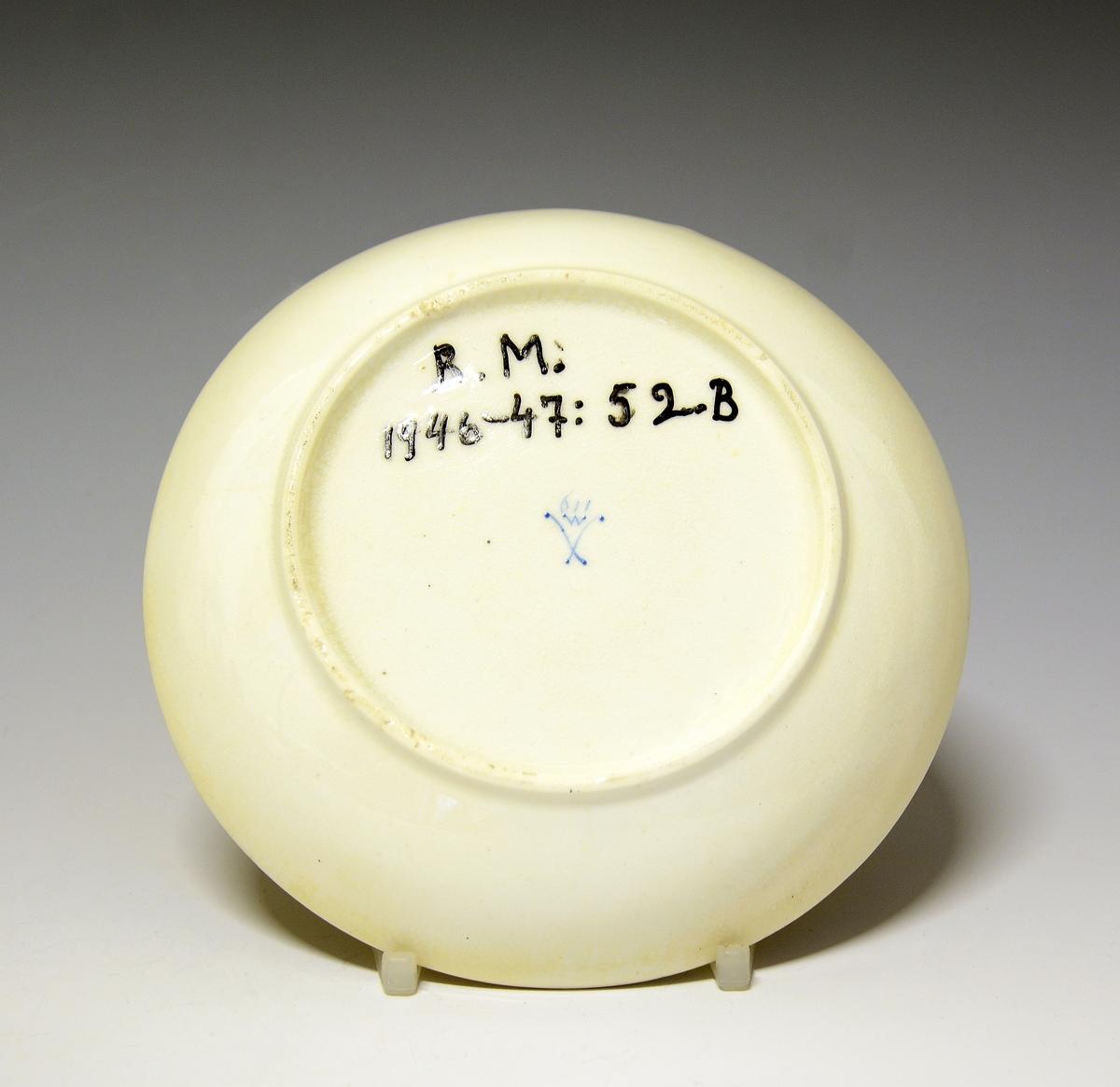 Fra protokollen:  Koppestell, 12 skaalir, 11 koppar (se A-L; registrert 1 kopp og 1 skål på hver bokstav, med unntak av L, som bare er skål). Alle same type og med same merke, men nokre kvite, andre gulvorne i glasuren. Kvart par med sereigne teikningar, motiv: landskap med hyttur, hus, borgliknande bygningar. Høgd, kopp 6 cm, tvermaal kopp ikr. 8,3 cm, skaal 14 cm. (Sume stekkir i, ein med skar).