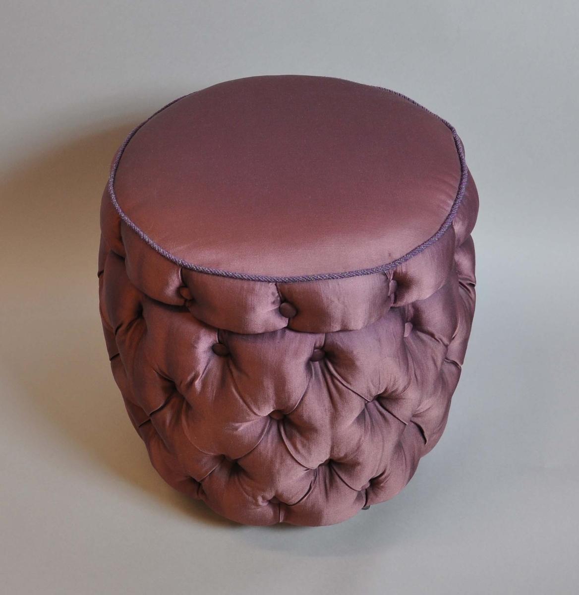 Puff med oppbevaringsrom. Puffen er trukket med silkelignende tekstil i lille farge. Puff og sete har innsydde, dekorative knapper. Puffen har tre hjul av metall. Setet er hengslet og kan åpnes, under setet er det et oppbevaringsrom.