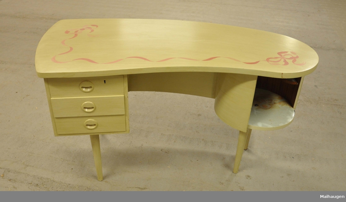 Bord av tre. Bordet har en avrundet bordplate og står på fire bein. På venstre side er det tre skuffer, den øverste med nøkkelhull. På høyre side er det en rund, roterbar hylle. På bordplaten er det dekormaling av rosa sløyfe. På baksiden av bordet er det to åpne hyller og en hylle med låsbar dør.
