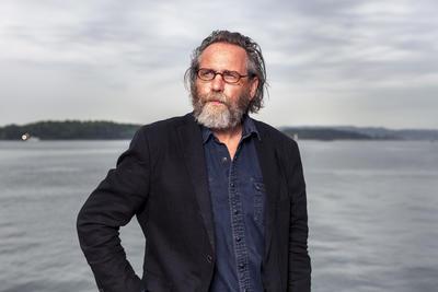 Forfatteren Fartein Horgar med briller og skjegg i svart jakke og blå skjorte, Oslofjorden i bakgrunnen.