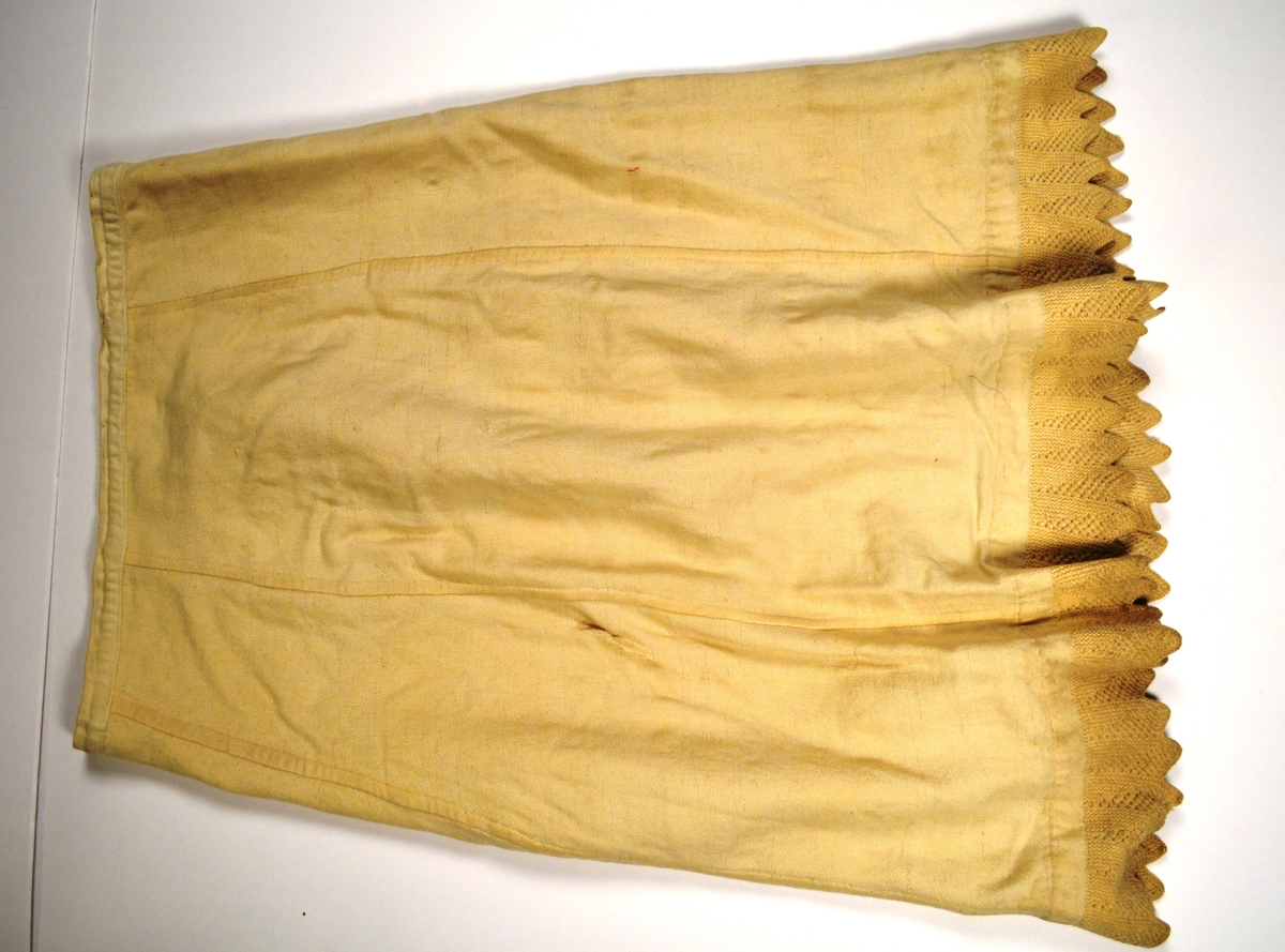Understakk i kypertvove kvitt og gul ulltøy. Sydd saman med indresaum av seks utskrådde høgder. Bomullslinning, med opning midt bak. Ei hekte, manglar krok.  Nede ein strikka tungebord.