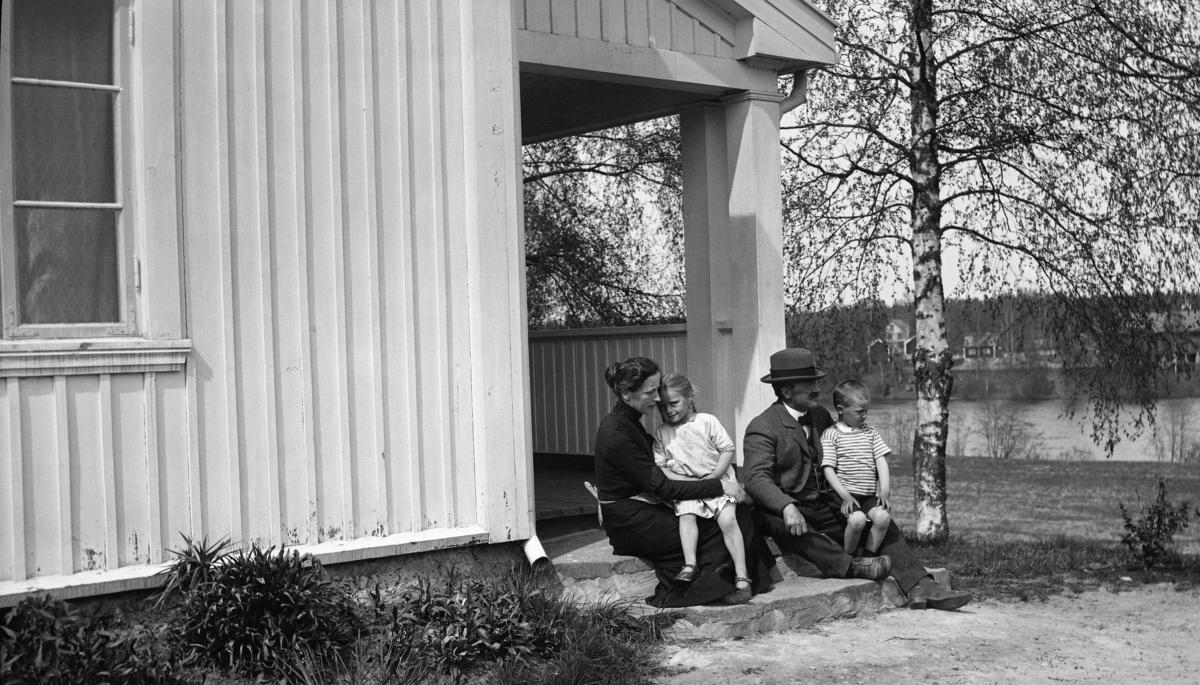 Familien Astrup fotografert sittende på trappa utenfor våningshuset på Haug i Våler i Hedmark.  Til venstre sitter mora i familien, Ludovica Astrup f. Fleischer, med dattera Anna Helene på fanget.  Til høyre ser vi familiefar Carl Astrup med sønnen Christian på kneet.  Carl og Ludovica Astrup kjøpte garden Haug med underbrukene Klyperud og Berg, samt seks skogteiger i Gåsvassdalen, i 1906.  Deretter satte de i stand bygningene på eiendommen.   Når det gjaldt våningshuset fikk de bistand av den kjente arkitekten Thorvald Astrup, en slektning av Carl.  I bakgrunnen til høyre ser vi vannspeilet på Glomma, og på motsatt side av elva skimter vi tunet på nabogarden Svenneby.  Carl Astrup var gardbruker, skogeier og tømmermerker.