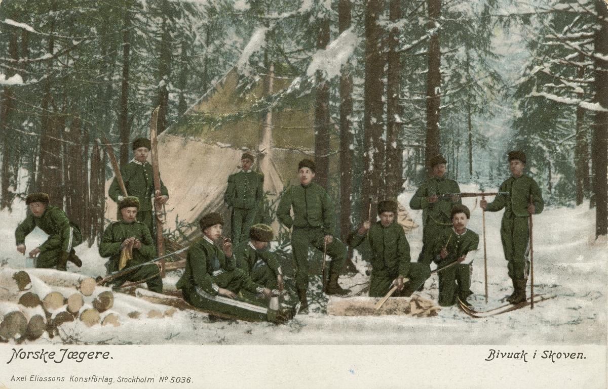 """Postkort. Det håndkolorerte fotografiet på kortets fremside viser 11 uniformerte norske soldater i vinterskog. Motivbeskrivelse påtykt kortets fremside: """"Norske jægere"""" og """"Bivuak i skoven""""."""