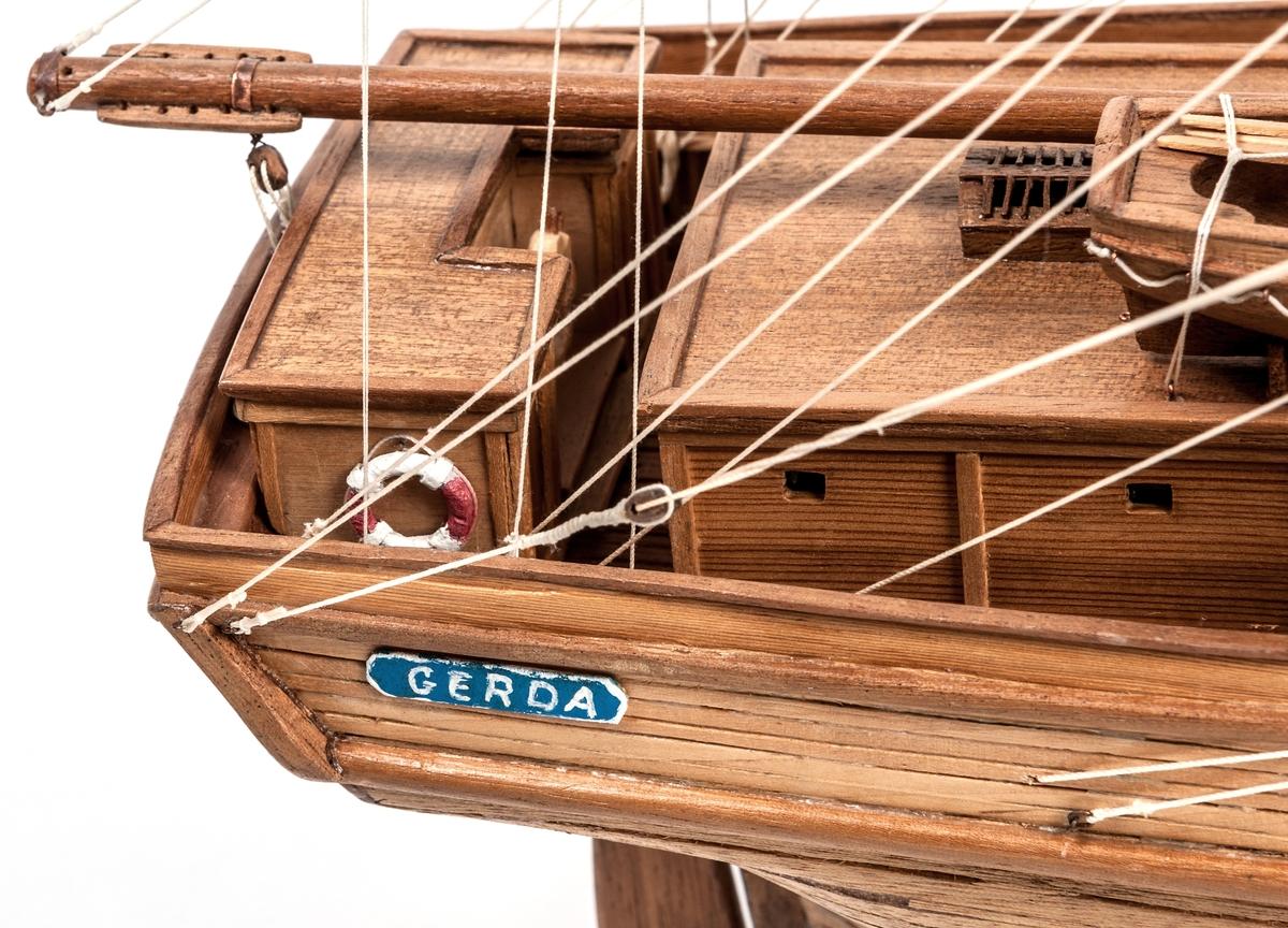 """Fartygsmodell, snaubrigg, i trä. Omålad. Akterpartiets sidor har blåmålade namnbrädor med vit text """"GERDA"""". Akterspegeln har en liknande namnbräda med texten """" GERDA-GEFLE"""". Därovan inom en grön eklövskrans ett kvinnohuvud mot blå botten. Originalet byggt 1869 i Gävle. Modell efter foto. Skala 1:60."""