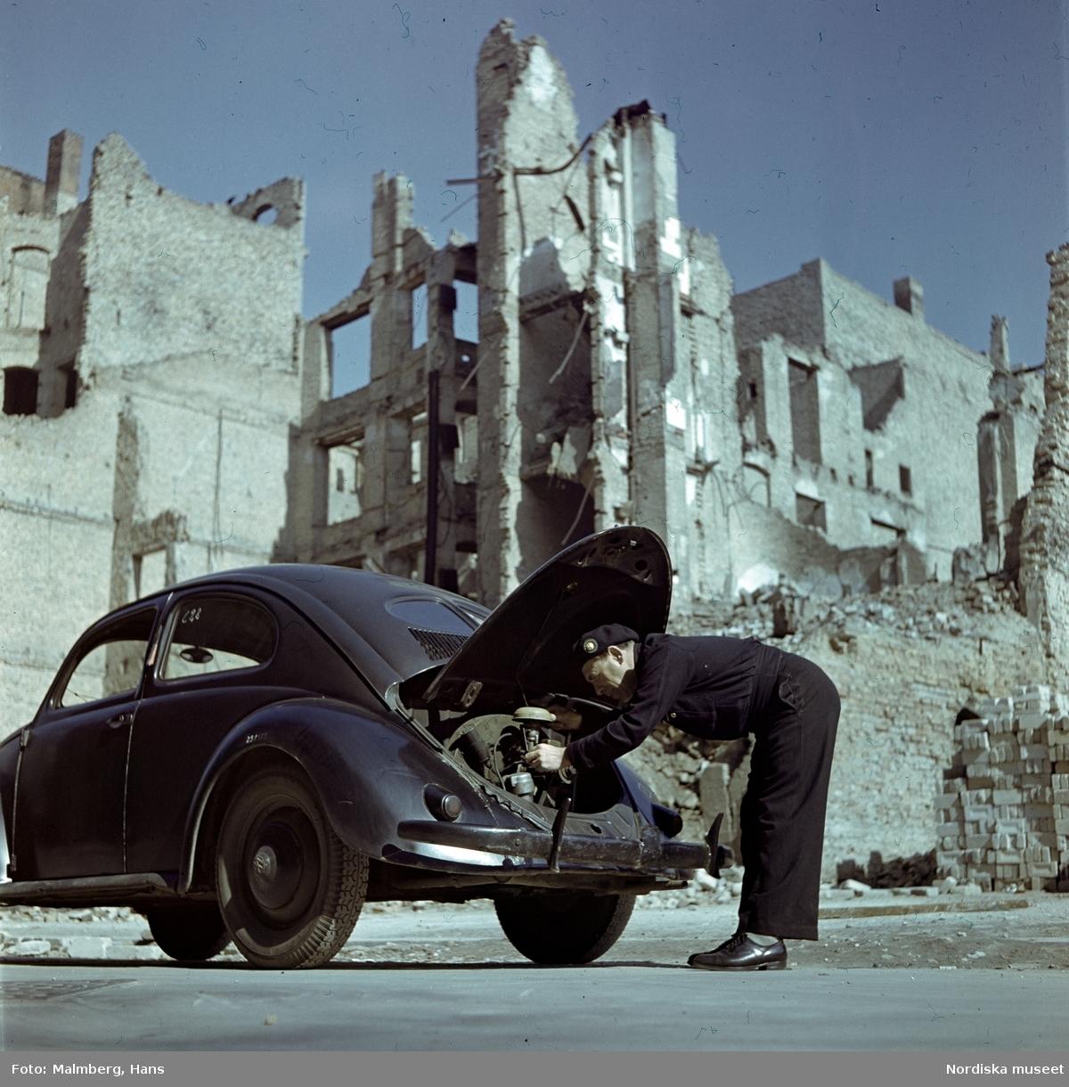 Berlin. En soldat ur de brittiska ockupationstrupperna kontrollerar motorn på en Volkswagen. Husruiner i bakgrunden.