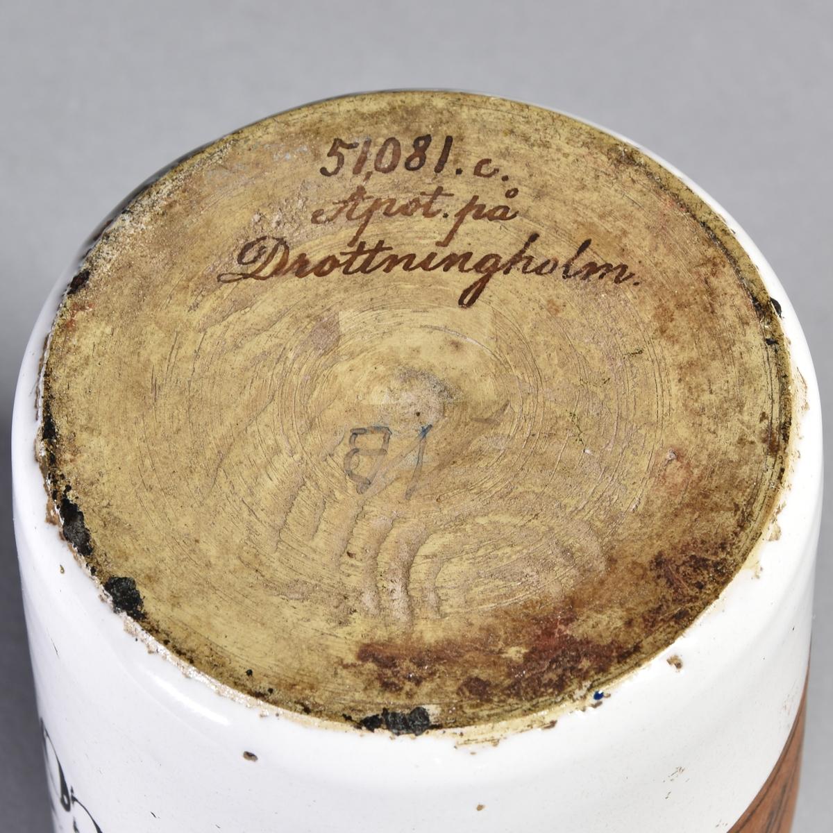 Apoteksburk av vitglaserad fajans, cylindrisk, med välvt lock med rund knopp. Sekundär etikett på baksidan.