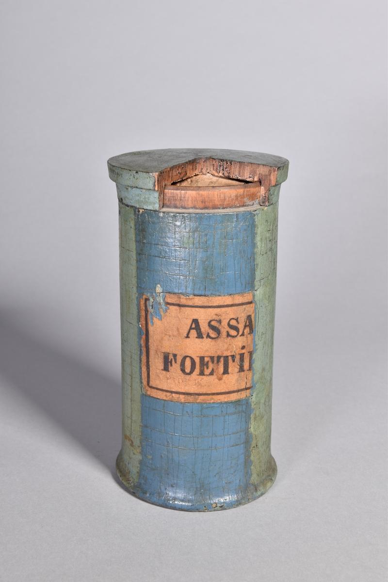 Ståndkärl av grönmålat trä, cylindriskt med plant lock. Svart text inom oval med bandrosett. Oläslig påskrift. Blåmålad baksida med sekundär etikett.