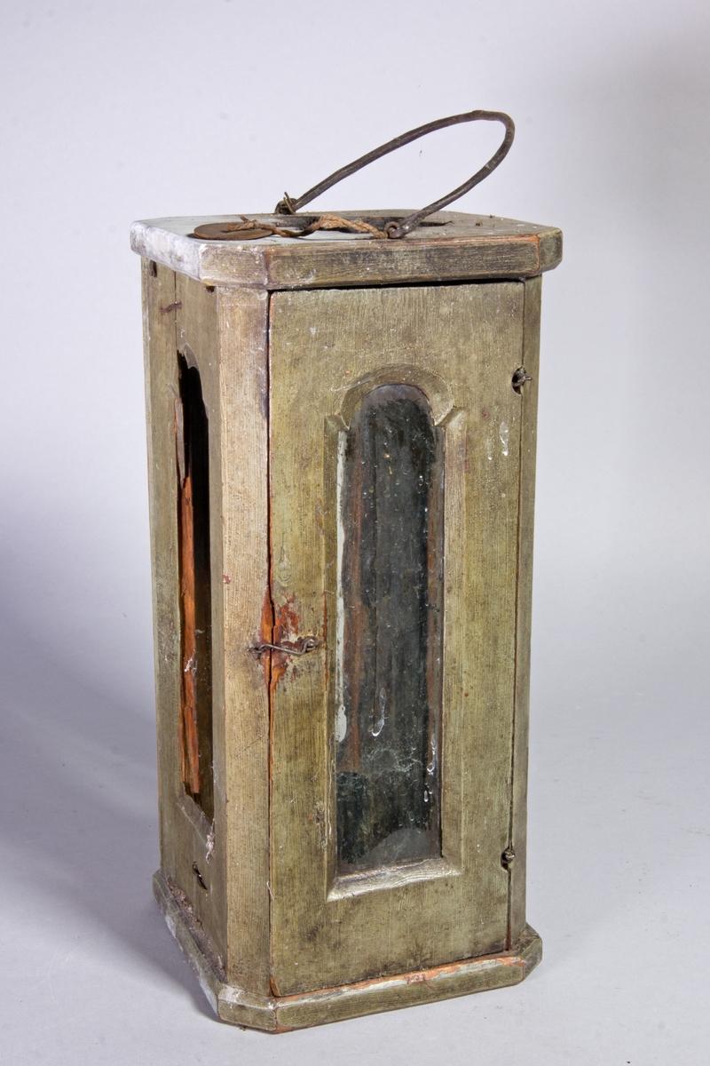 Ljuslykta av trä, målad, stående rektangulär, med glasade sidor. En sida öppningsbar. Järnten för upphängning.