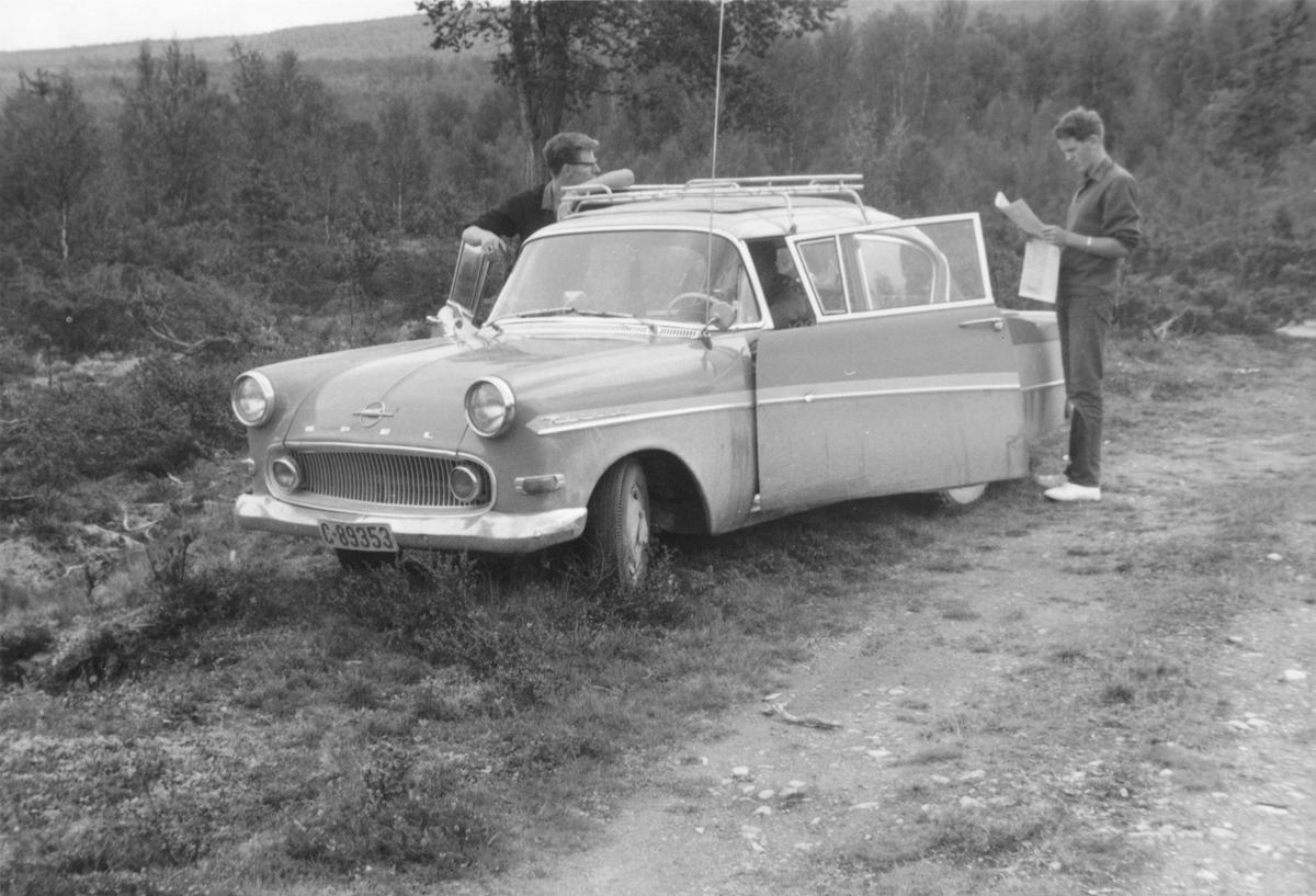2 unge menn på biltur i skogen. Leser kart.