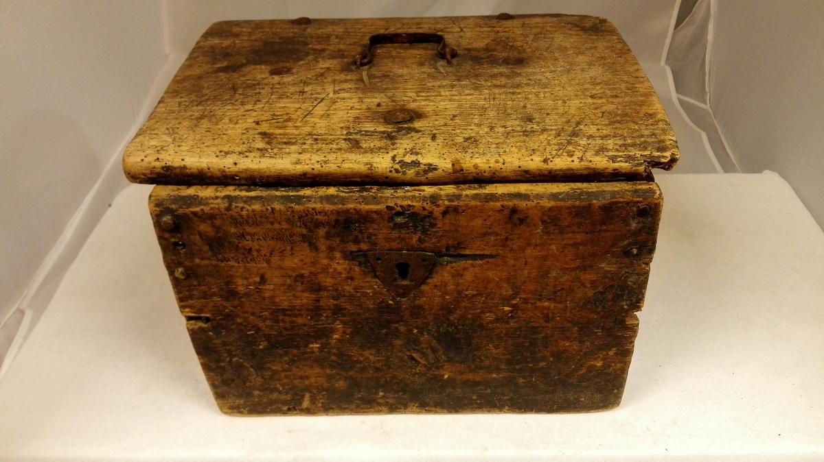 Form: Firkanta. 1 nisteskrin.  Firkantet nisteskrin med hængslet laag og hank av jern på laaget. Sammensat med trænagler. Laas mangler. Av furu. Uten utskjæringer eller forsiringer. Umalt. Længde, høide og bredde: 33,7,  25,5 og 26 cm. Indvendig indskaaret 1773.  Gave fra Ole Maalsnæs, Kvamsø.