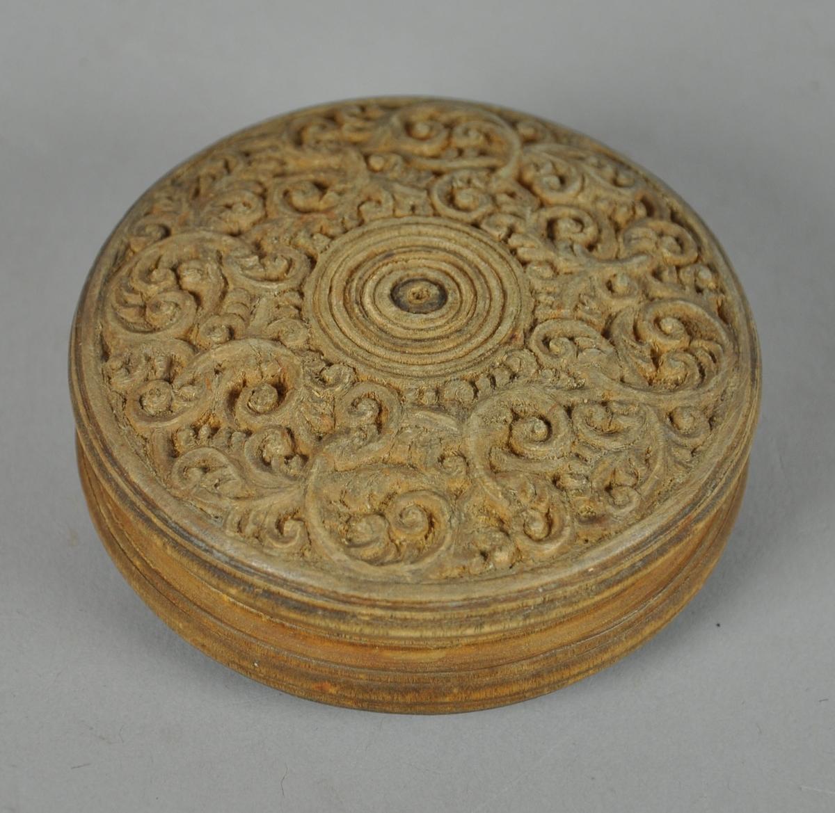Rund eske av tre, med skjært dekor på over- og undersiden. På lokket er det skjært dekor med motiv av konsentriske sirkler med akanuslignende spiraler rundt. På undersiden av esken er det skjært dekor med motiv av rutenett i en sirkel, med akantuslignende spiraler rundt.