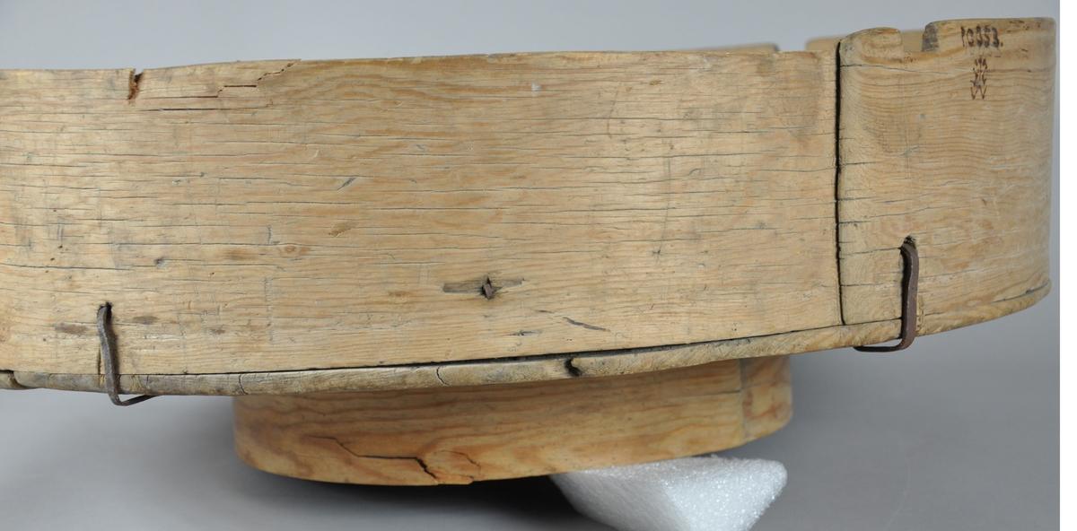 Brødfat med sveipet treverk. Fatet har rund form og består av sideplate, bunnplate og stett under bunnplaten. Sideplaten og stetten er hver for seg sveipet med et helt trestykke. Bunnplaten er satt sammen av 3 plater, 2 store og 1 liten. Bunnplaten har mørknet til på grunn av fukt eller annen type slitasje. Sideplaten har innhakk i treverket som tyder på at det originalt har hørt med et lokk. Sideplaten er festet til bunnplaten med jernarmeringer.