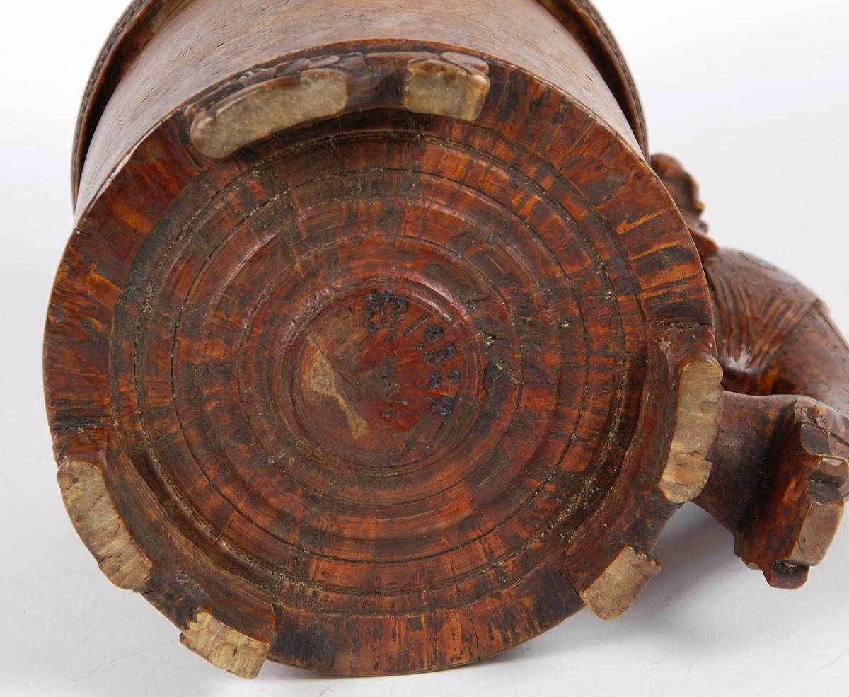 Kanne av dreid valbjørk. Lokk med kronet løve omgitt av en dobbel bord, utenfor borden er utskåret bokstavene G, J, S, H, A og årstallet 1832, ytterkanten med utskåret bord. Lokkåpner formet som løve med krone. Tre løveføtter.