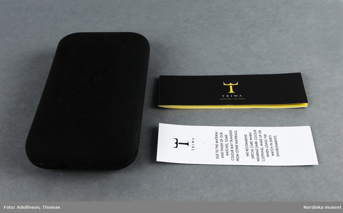 """Etui (A-C)  A) Plastetui för klocka. på lockets utsida intryckt företagets logo (ett T med tre toppar på.) Gjutet, rundade hörn. Inuti formgjuten insats för klockan.  B) I etuiet ett llitet häfte om företaget och hur klockan ställs in och justeras. Svart utsida med gulttryck, bladen är gula med svart text.  C) I botten en lapp med texten  """"TRIWA DUE TO THE MATERIAL AND FINISH OF OUR WATCHES, SOME COLOUR MAY TRANSFER FROM OTHER MATERIALS.  WE RECOMMEND SPECIAL CARE WHEN WEARING DARK COLOUR CLOTHING', MAKE UP OR WHEN USING THE  WATCH IN DIRTY ENVIRONMENTS.""""  Hör ihop med 332.981 och 332.982 /Magdalena Fick 2011-12-02"""