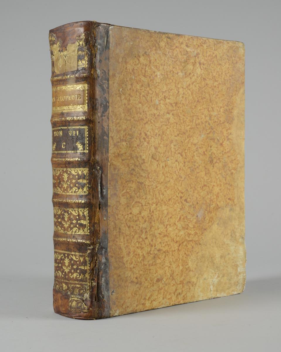 """Bok, """"Encyclopedie ou dictionnaire raisonné des sciences, des arts et des métiers"""" av Diderot och d`Alembert, utgiven 1778. Tredje upplagan, vol. 7. Halvfranskt band med pärmar av papp med påklistrat marmorerat papper, rygg av skinn med fem upphöjda bind med guldpräglad dekor, blindpressad och guldornerad rygg, titelfält med blindpressad titel och ett mörkare fält med volymens nummer. Påklistrad pappersetikett med nummerbeteckning med bläck, skadad. Med rött snitt."""