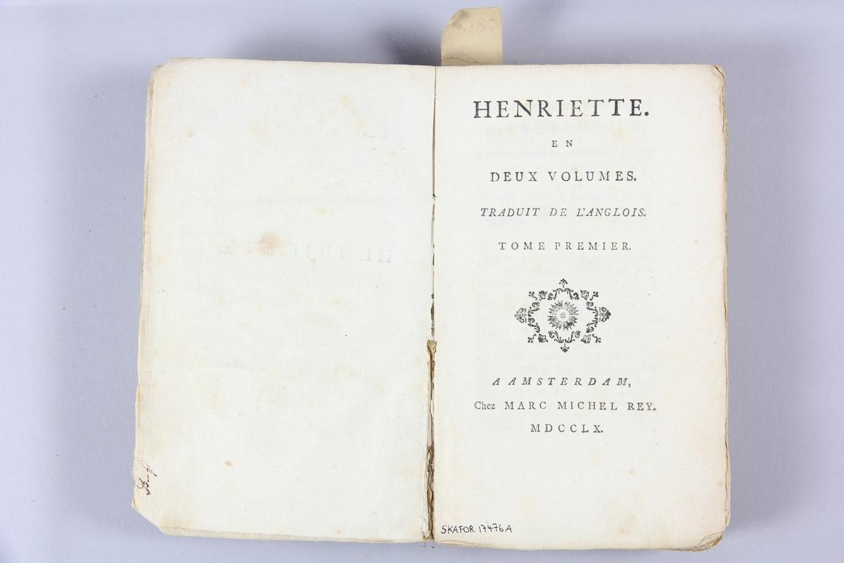 """Bok, pappband, """"Henriette"""", del 1, tryckt 1760 i Amsterdam. Pärmar av  gråblått papper, rygg med etikett med bokens titel, delvis svårtolkad. Oskuret snitt. Anteckning om inköp på pärmens insida."""