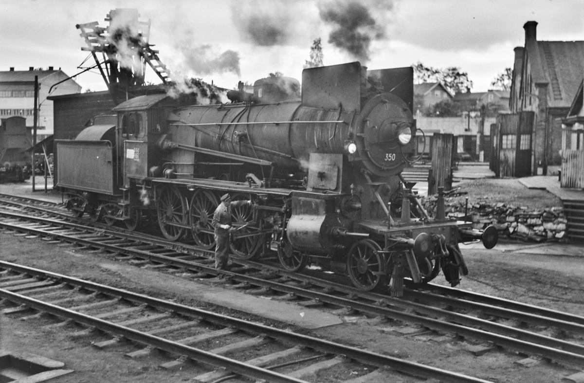 Damplokomotiv type 30b nr. 350 ved lokomotivstallen på Hamar stasjon. Lokomotivfører med smørekanne.