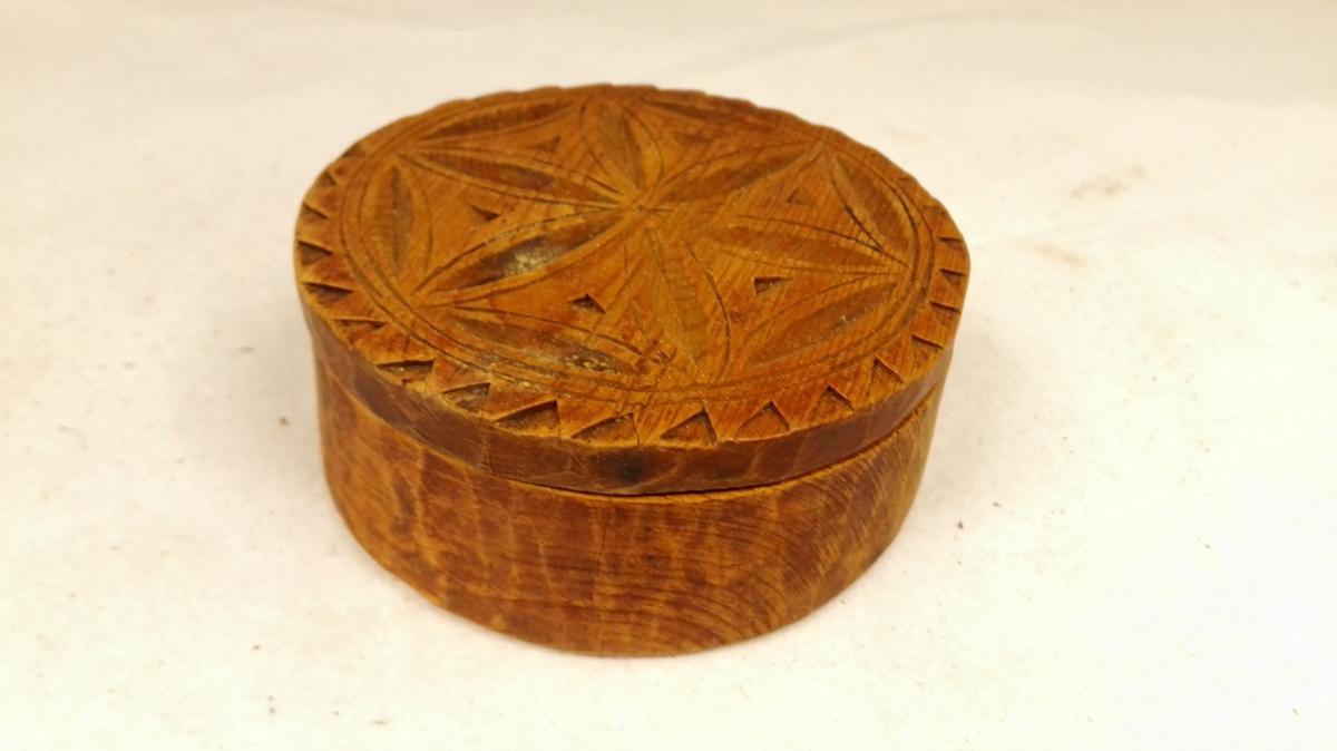 1 æske  Rund spikket æske av furu, oprindelig malet brunröd. Paa laaget en karveskurutskjæring og under bunden strekornamenter. Diam. 9,6 cm. Samtlige disse gjenstander (12381 - 97) har tilhört sergeant H.P. Seim, Seimsdalen.  Gave fra enken Durdei Seim, Seimsdalen, Aardal