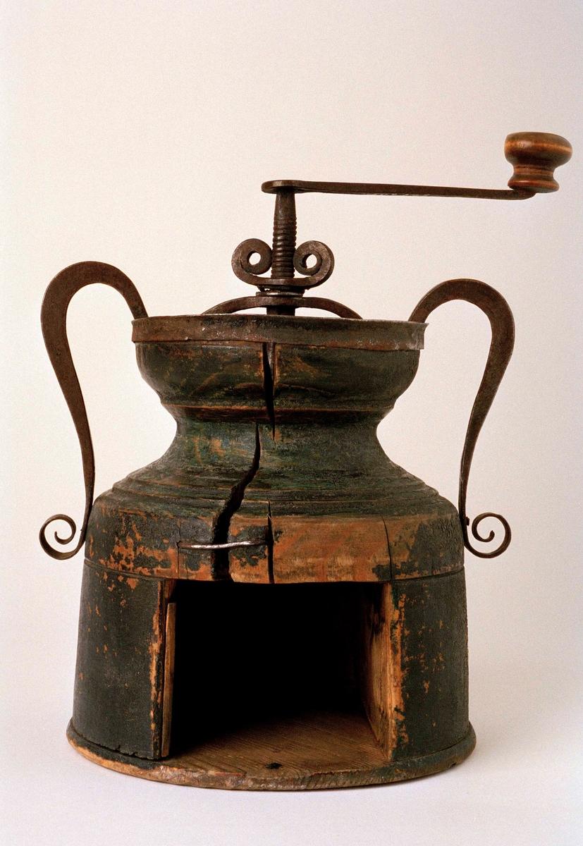 Rund, svarvad kaffekvarn av trä, två lodgrepen, vev och vingmutter av smidesjärn. Målad grön (?) , lådan saknas, spräckt och lagad med nit, vevens handtag av trä sliten in mot mitten.