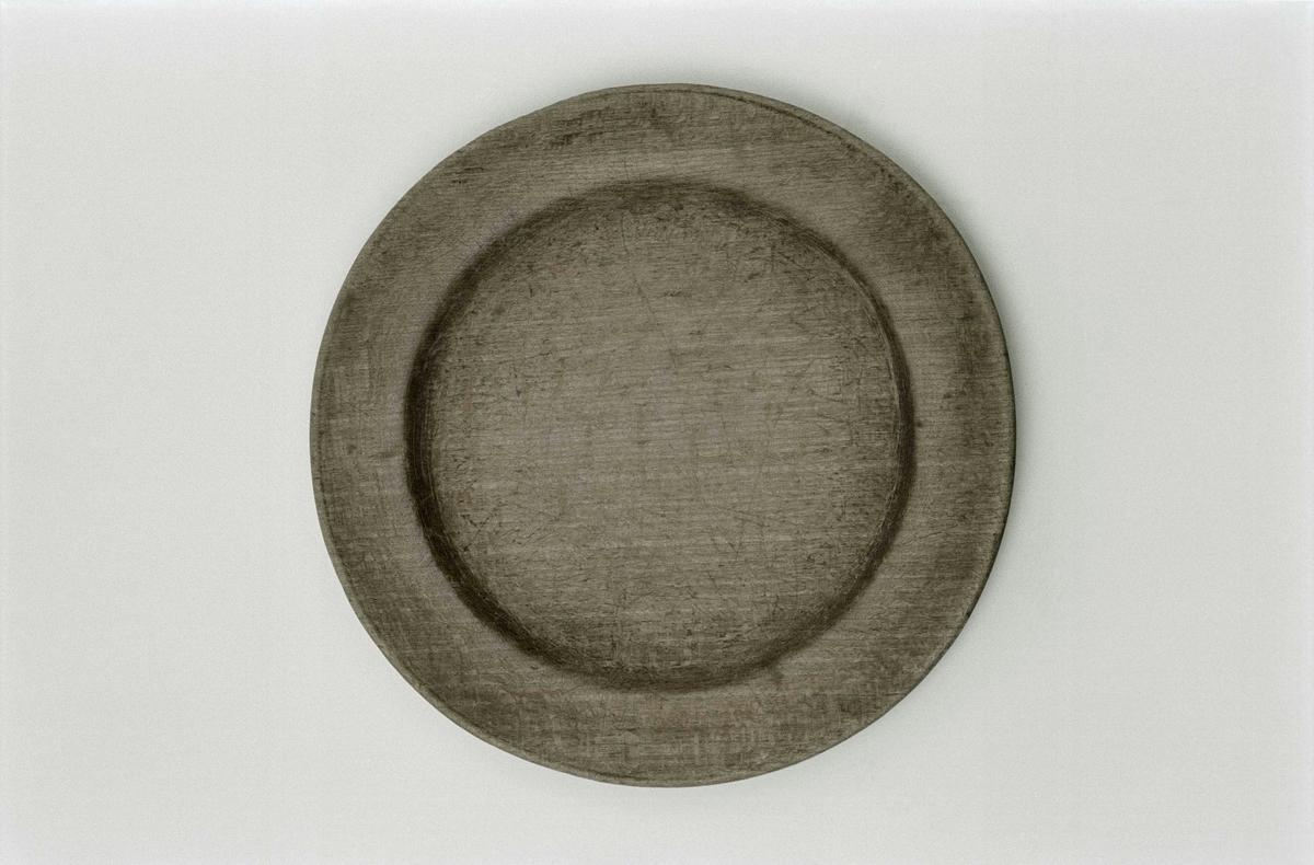 Svarvad tallrik av bokträ, flat, svarvad fåra på brättet som delvis är utnött. Två karvade bomärken.