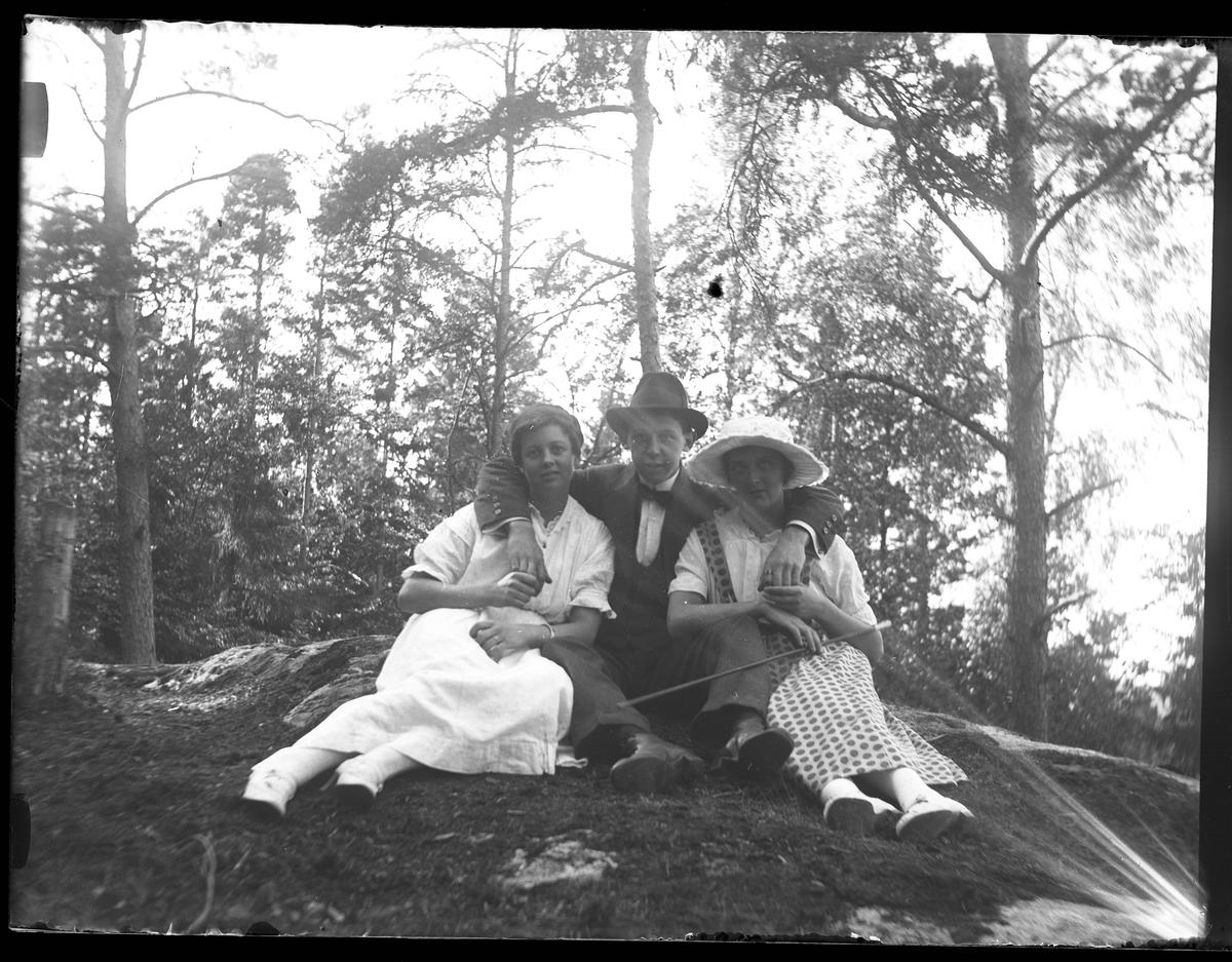Ella, Hugo Larsson och Ellen fotograferade i Nolhaga. Ella och Ellen är ljust klädda och i mitten sitter Hugo och håller om dem.