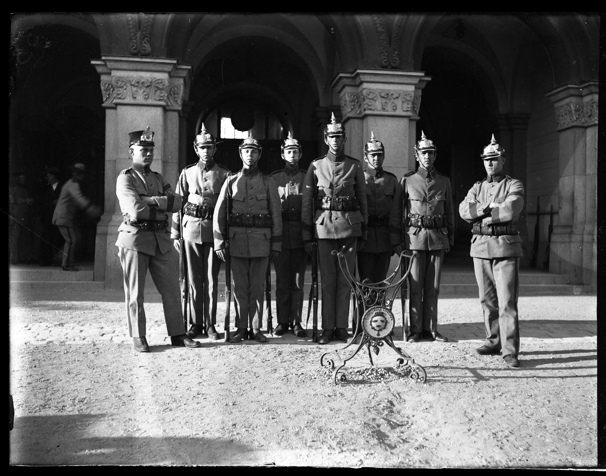 Gruppbild på livkompaniets (I1) kasernvakt i grå uniformer, hjälmar och vapen.