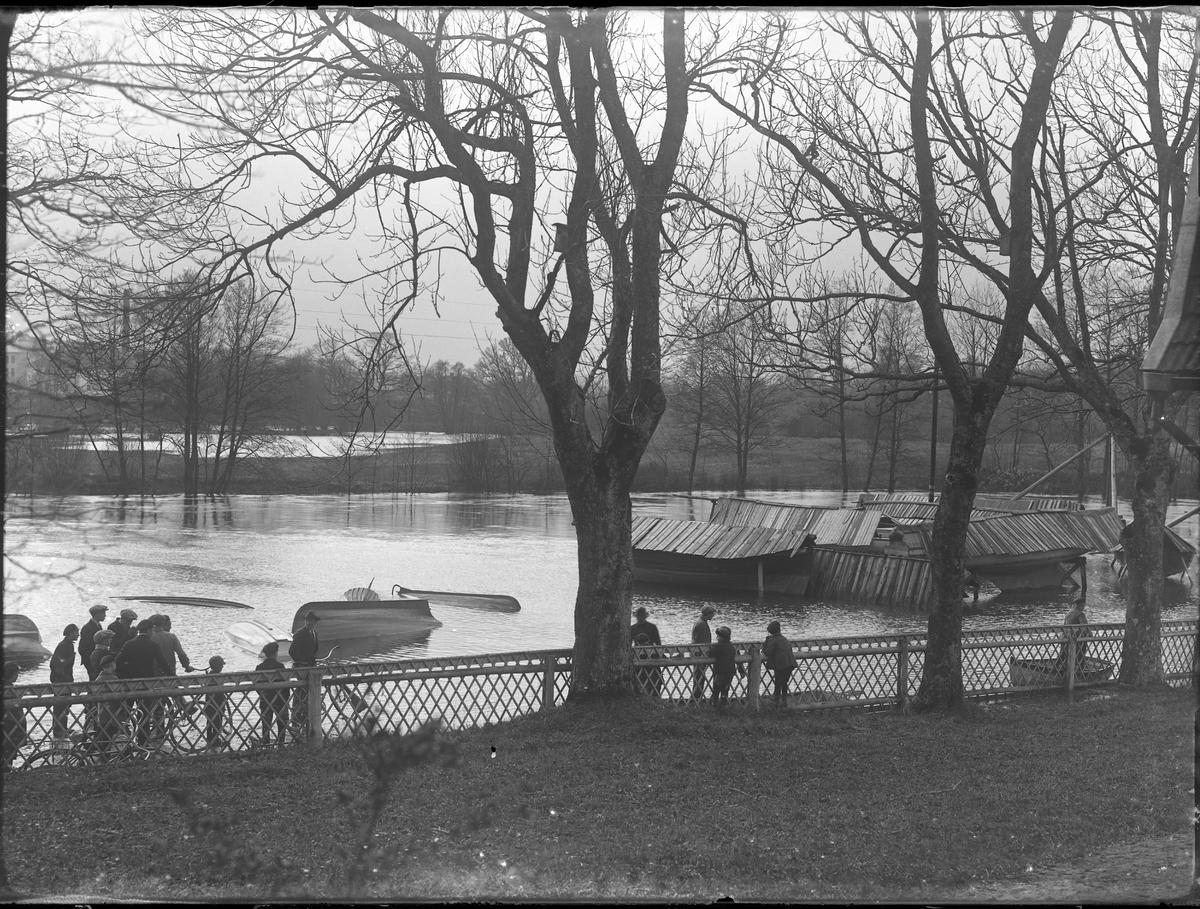 Män och barn står och tittar på översvämningen vid Lugnet. Delvis under vattnet ligger båtar som tagits upp på land för säsongen.