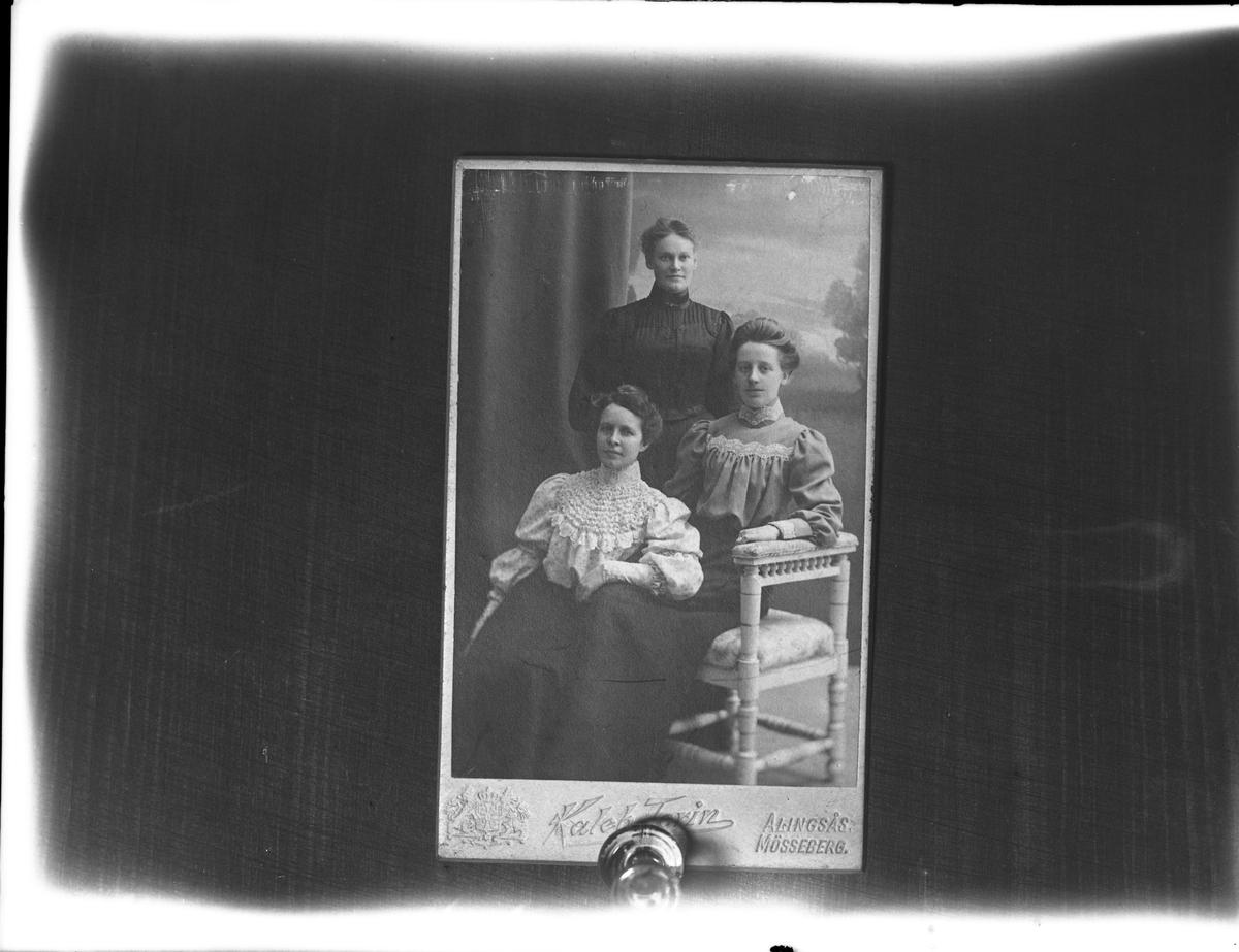 """Reprofotografi av ett ateljéporträtt taget hos Kaleb Torin. Porträttet föreställer tre kvinnor och är troligen taget runt sekelskriftet. Reprofotografiet är en beställning från """"Anna""""."""
