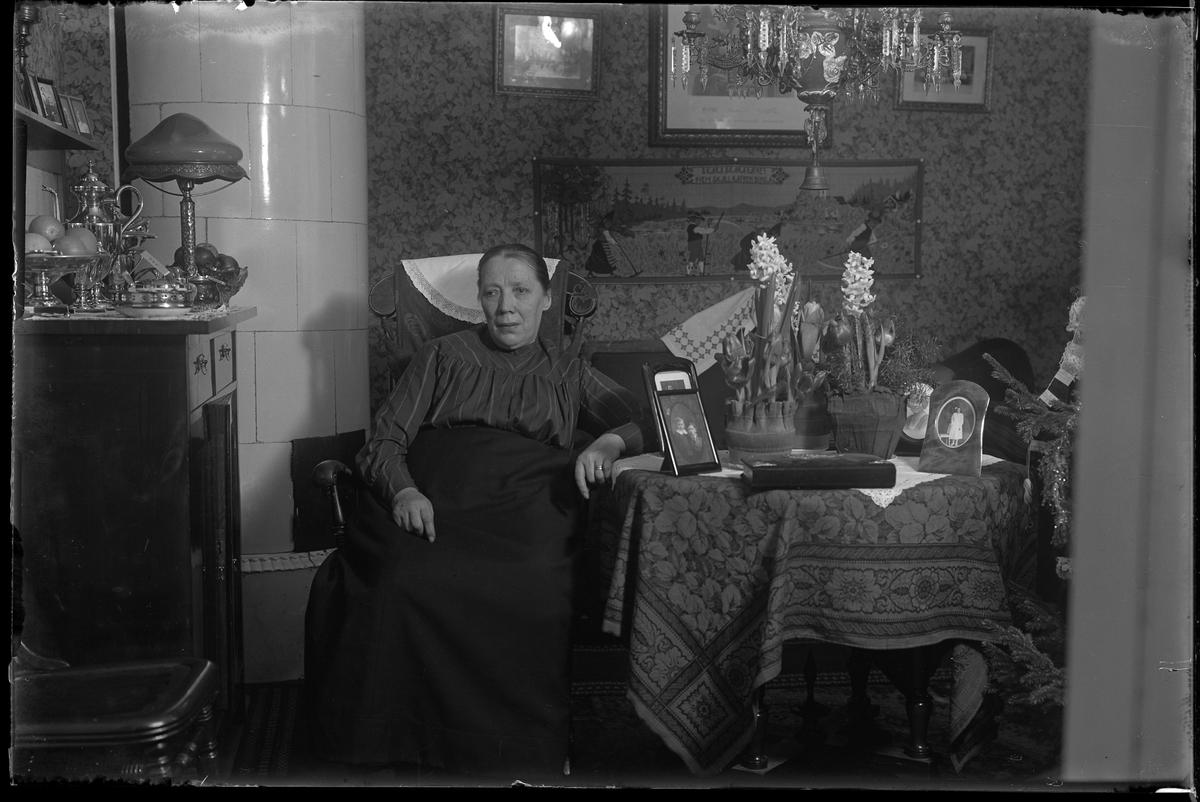 Fru Johansson fotograferad i samband med sin 60årsdag. Hon sitter i en gungstol i ett vardagsrum och på bordet bredvid henne står hyacinter och porträttfotografier. På hennes andra sida står en skänk med föremål av nysilver ovanpå. I hörnet finns en vit kakelugn.