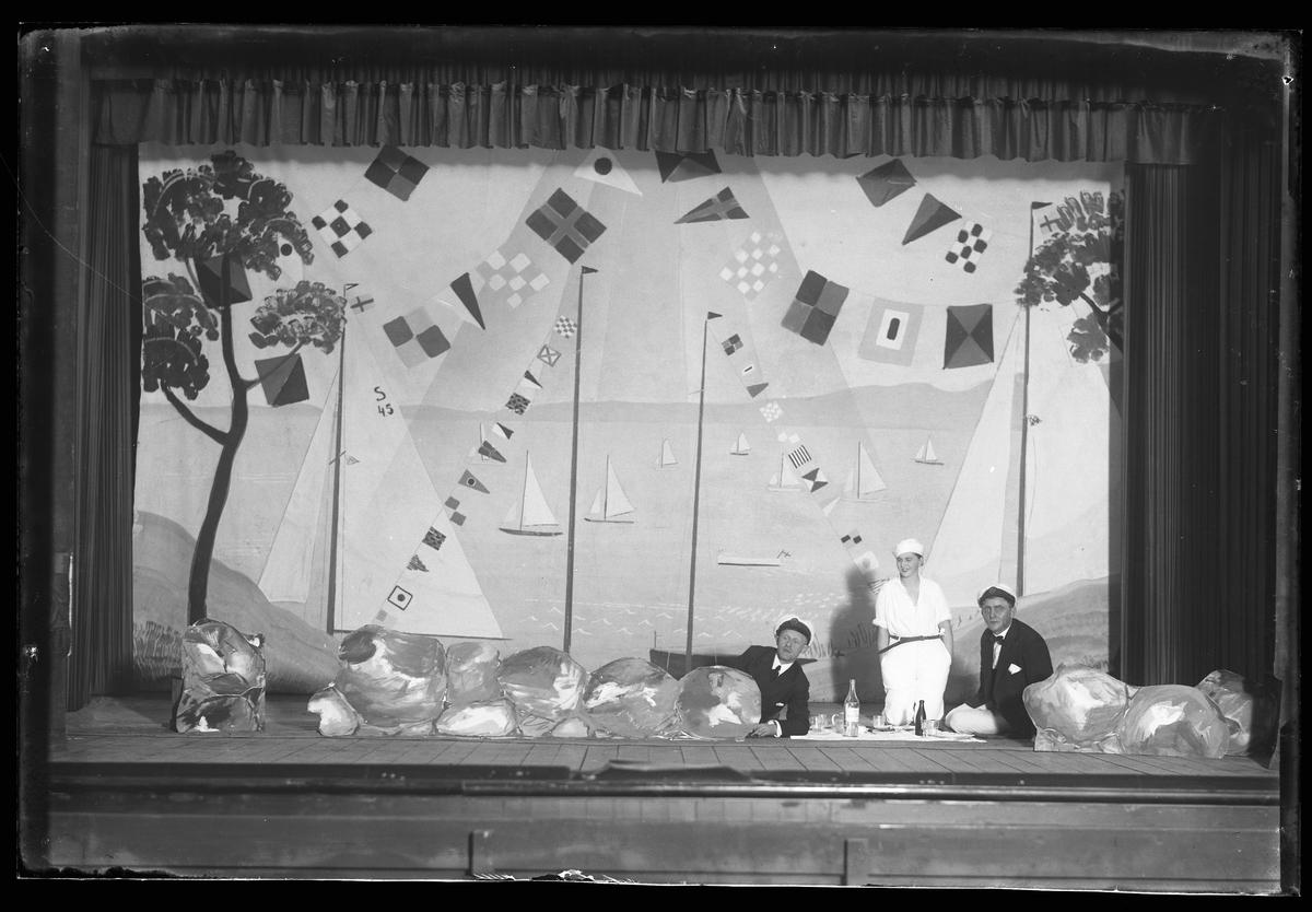 Två män och en kvinnar på en scen spelar nyårsrevy.