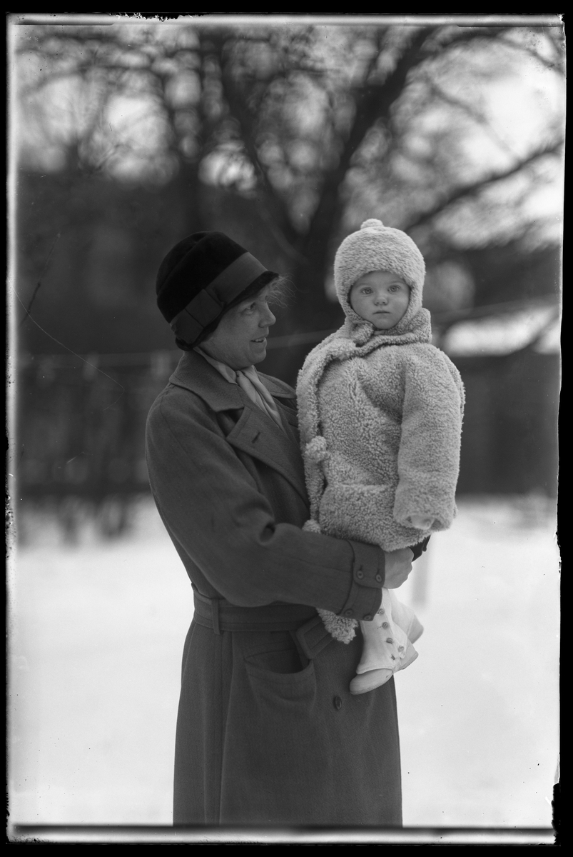 """Fru Berg, tolkad som Gerda Teresia Amalia Berg (f. Norgren) håller sin dotter, tolkad som Elsa Margareta Berg. Flickan har damasker och vinterkläder av päls. I fotografens anteckningar står det """"Ing[enjör] Bergs flicka med fru Berg""""."""