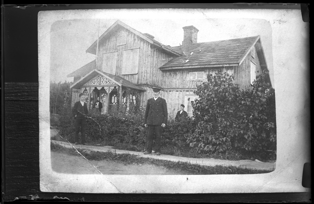 Reprofotografi av fyra personer som står framför ett trähus. Huset har två våningar och en veranda med snickarglädje. En kvinna står på verandan med en katt i handen. Vid ena fönstret står en man och utanför häcken, på gatan står ytterligare två män.