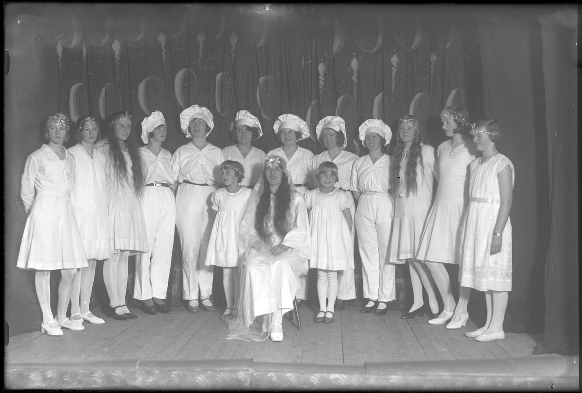 Tolv kvinnor står på rad på en scen, utklädda till sockerbagare eller tärnor. Framför dem sitter ytterligare en kvinna, som Lucia, och vid sidan om henne står två flickor. Bilden tagen vid Socialdemokraternas kvinnoklubbs Luciafest. Sara Fransson (född Strandberg) står som femma från vänster och var 25 år vid fototillfället.