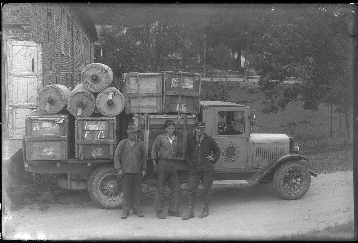 """Tre män fotograferade vid en lastbil med Alingsås Bomullsväveris logga på framdörren. På flaket syns packlådor samt tygrullar märkta """"Nääs""""."""