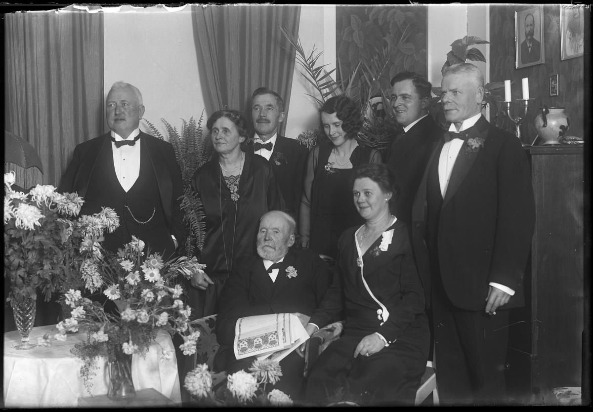 """En man omgiven av nära och kära sitter i en stol och håller i telegram. Bilden är tagen i samband med hans födelsedag. I fotografens egna anteckningar står det """"Kvarnström 90år"""", tolkat som Anders Magnus Kvarnström."""