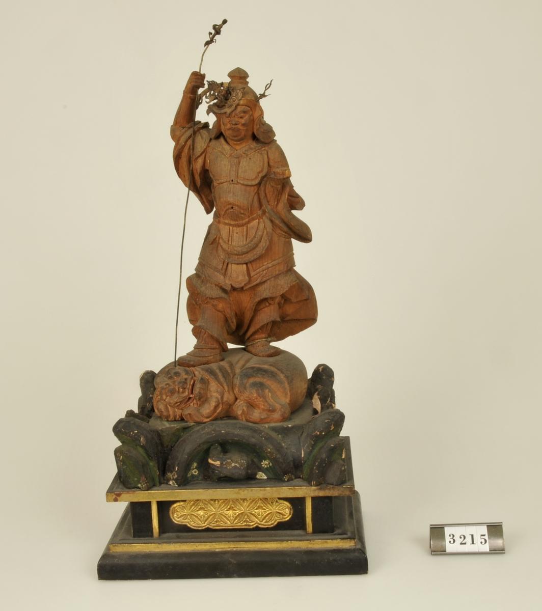 Krigsgud. Skuren i trä. Monterad på skulpterat fotfäste.  Har tillhört de Adelsköldska samlingarna.