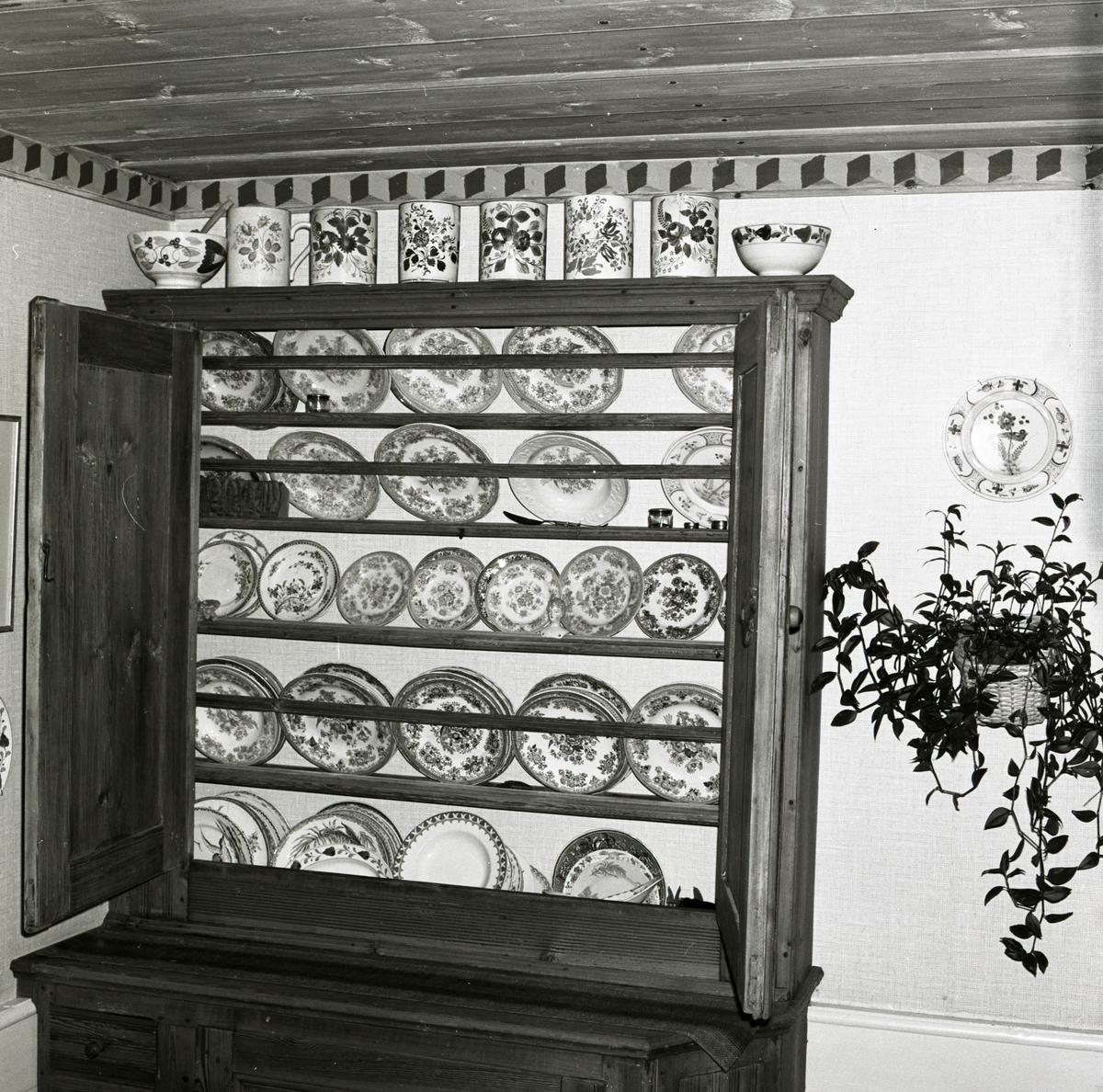 I ett rum på gården Sunnanåker står ett skåp med porslinstallrikar, 1972.