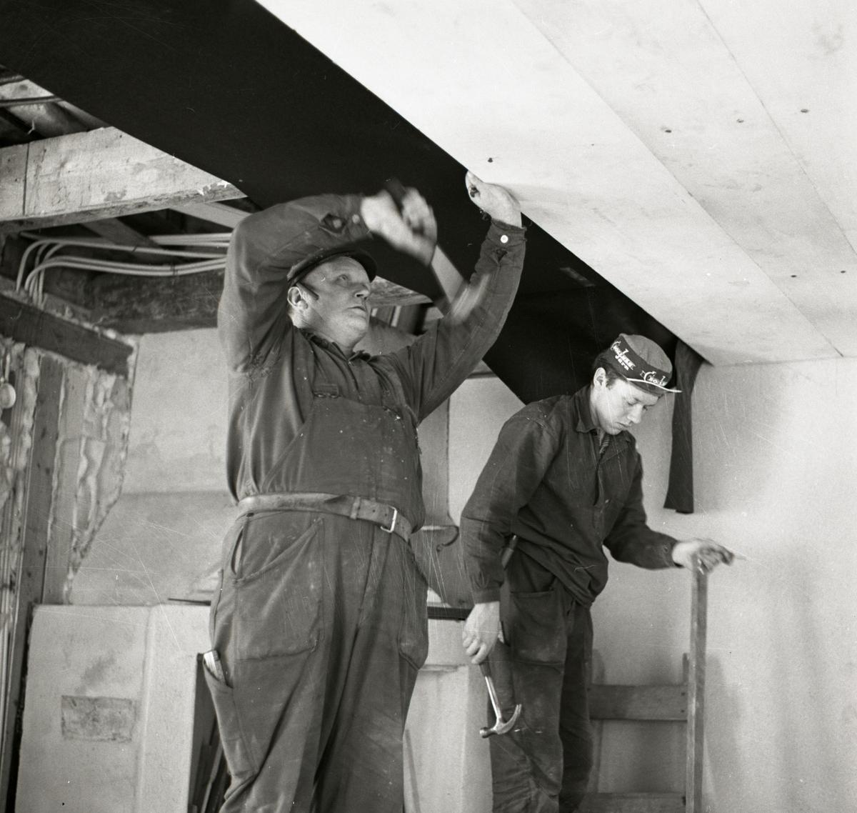 Två män spikar upp takpanel i ett hus på gården Sunnanåker, 1967.