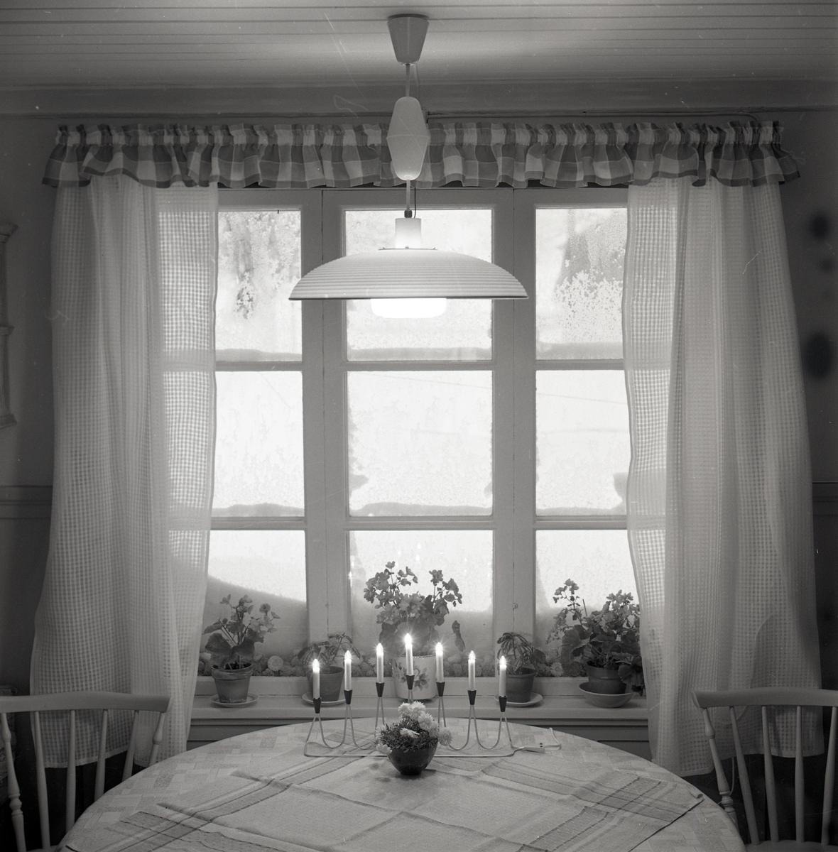 Ett fönster med gardiner bakom ett bord dekorerat med en adventsljusstake i december 1968.