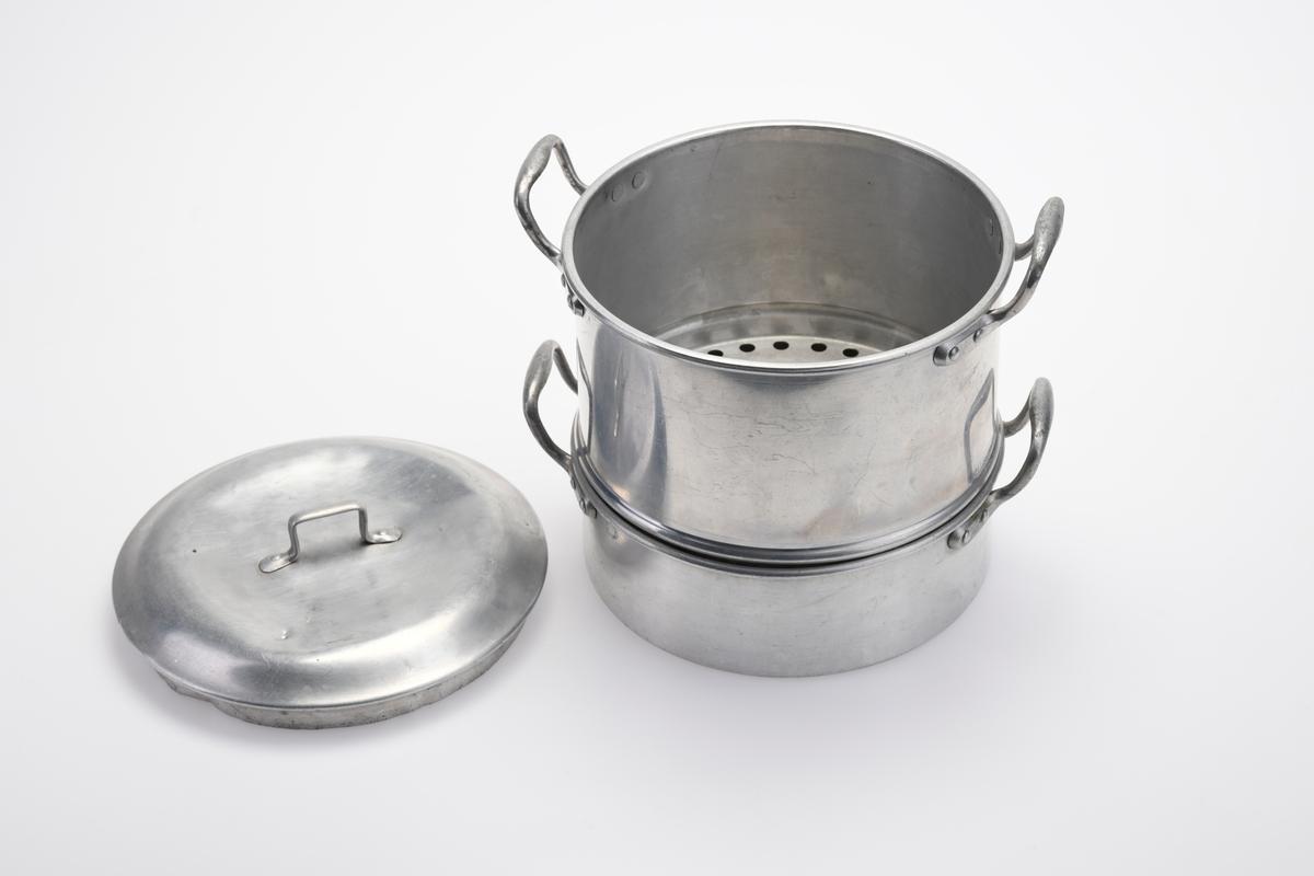 En kasserolle/dampkoker i tre deler. FTT.56056.01: Et rundt lokk laget av aluminium. Oppå lokket er det festet et håndtak med nagler. FTT.56056.03: Midtdelen av kasserollesettet som også er laget av aluminium. I bunnen er det stanset ut hull (hele bunnen er gjennomhullet). I sidene er det festet hanker som står rett opp. Hankene er festet med nagler. FTT.56056.02: Bunndelen av kasserollesettet som også er laget av aluminium. I sidene er det festet hanker som står rett opp. Hankene er festet med nagler. Til sammen blir dette en dampkoker.