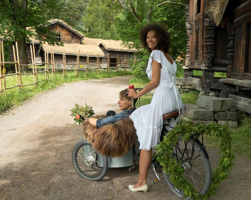 Tidenes bryllup på Norsk Folkemuseum, brud som kjører brudgom i gammel lastesykkel
